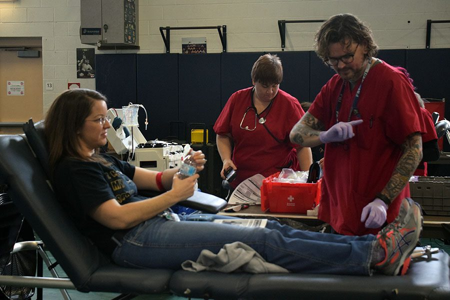 A blood drive volunteer explains to Mrs. Diamantopoulos what to be aware of after donating blood.